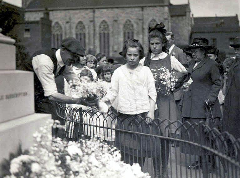 A child with floral tributes at the Upper North Street School war memorial unveiling ceremony, Jun 23 1919