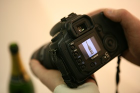 Photo of hands holding a camera displaying a photo that has already been taken in the foreground and the top of a blurred bottle in the background.