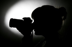 a side view photo of a silhouette of a women holding a camera to her face